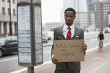 "Young businessman holding ""Will Work for Food"" sign at street"