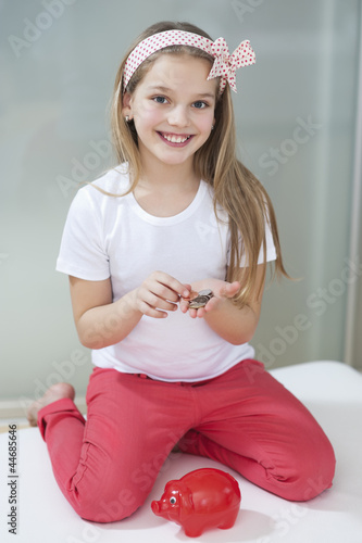 Portrait of girl with piggy bank and coins sitting in bed