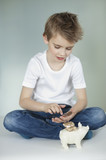 Boy with piggy bank counting coins over gray background