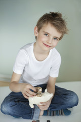 Portrait of young boy putting coin in piggy bank