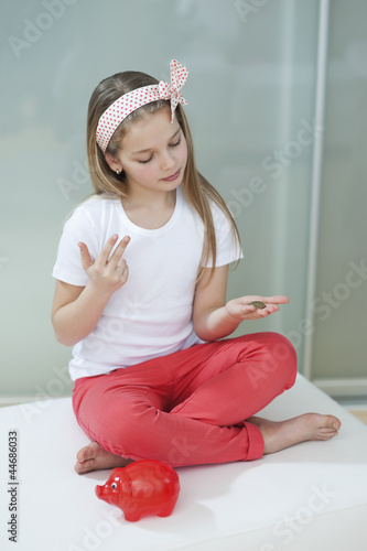 Girl with red piggy bank counting coins on bed