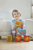 Portrait of cute little boy stacking blocks while sitting on floor