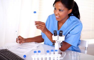 Ethnic scientific woman working with test tube