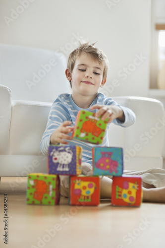 Little boy stacking blocks while sitting on floor
