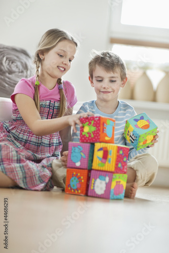 Children stacking blocks while sitting on floor