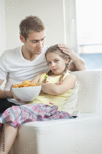 Father convincing daughter to eat wheel shape snack pellets
