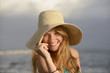 blond woman with sunhat on the beach