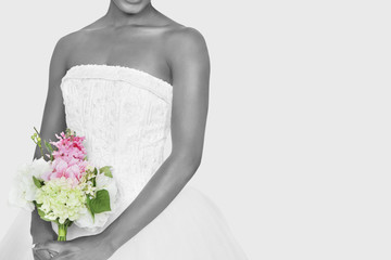 Midsection of bride holding bouquet over gray background