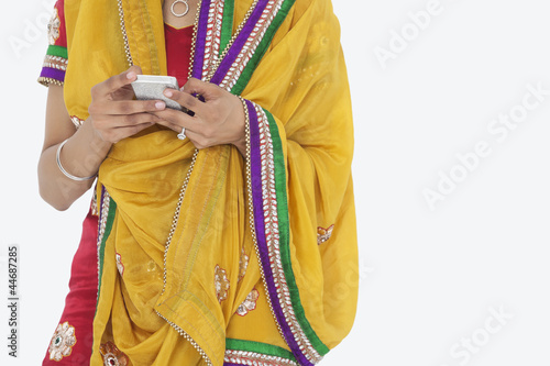 Midsection of woman in Indian clothing using cell phone over white background