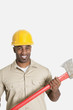Portrait of happy African male construction worker holding axe over gray background