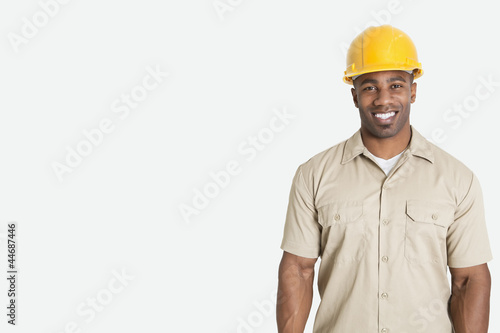 Portrait of happy young African man wearing yellow hard hat helmet over gray background