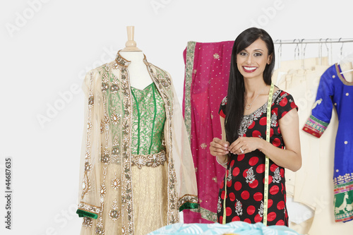 Portrait of Indian female dressmaker standing by a dummy dressed in traditional wear