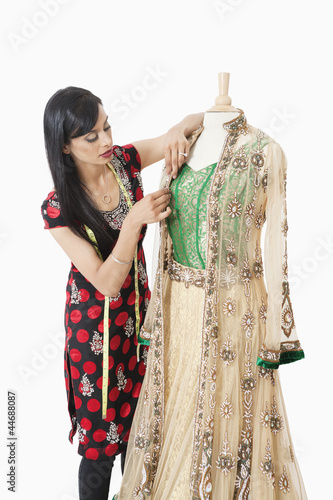 Indian female dressmaker working on a traditional outfit over gray background