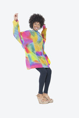 Full length portrait of happy African American woman in dashiki dancing over gray background