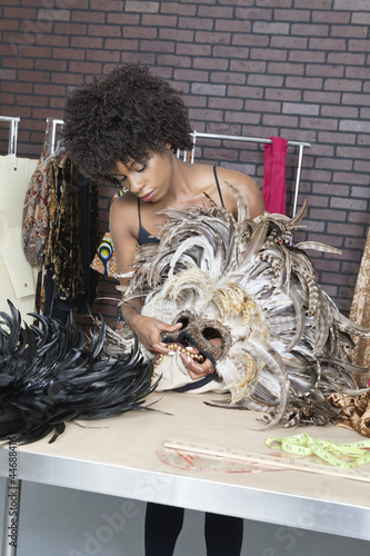 African American female fashion designer working on feather mask