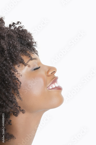 Profile view of an African American woman smiling with eyes closed against gray background