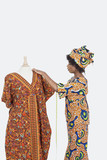 Female tailor in traditional outfit measuring dashiki on tailor's dummy over gray background