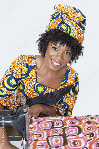 Portrait of an African American female fashion designer sewing fabric over gray background