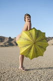 Portrait of a happy naked woman with yellow umbrella on barren landscape