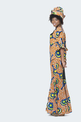 Full length portrait of young woman in African print attire standing over gray background