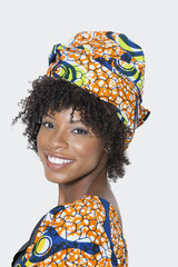 Portrait of young woman in African print attire looking over shoulder against gray background