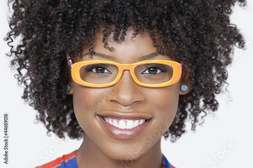Close-up portrait of an African American woman wearing glasses over gray background