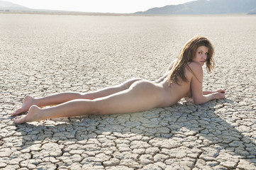 Naked young woman lying on cracked arid landscape