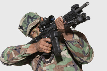 US Marine Corps soldier aiming M4 assault rifle against gray background