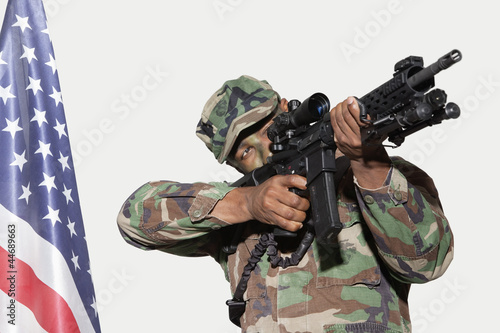 US Marine Corps soldier aiming M4 assault rifle with American flag against gray background