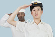 Portrait of serious female US Navy officer and male sailor saluting over light blue background