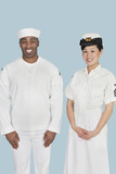 Portrait of happy female US Navy officer with male sailor over light blue background