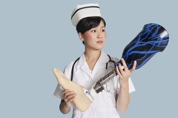 Female doctor holding prosthesis foot over light blue background