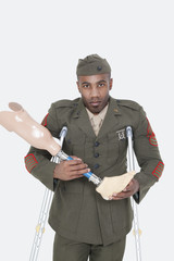 Portrait of a disabled US military officer holding prosthesis leg over gray background