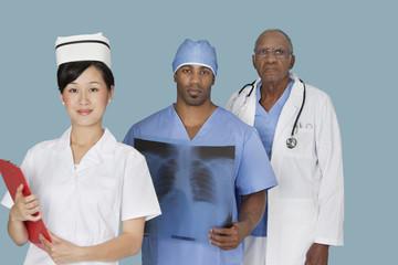 Portrait of three multi ethnic medical professionals over light blue background