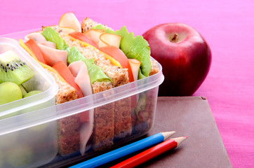 Healthy school lunch of sandwich fruit with pencils and book