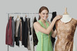 Portrait of beautiful female fashion designer adjusting cloth on tailor's dummy