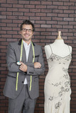 Portrait of mature male fashion designer standing next to tailor's dummy