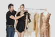 Mature male fashion designer adjusting dress on model in design studio