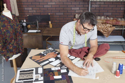 Mature male fashion designer working on sketch in design studio