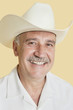 Portrait of happy senior man wearing cowboy hat over yellow background