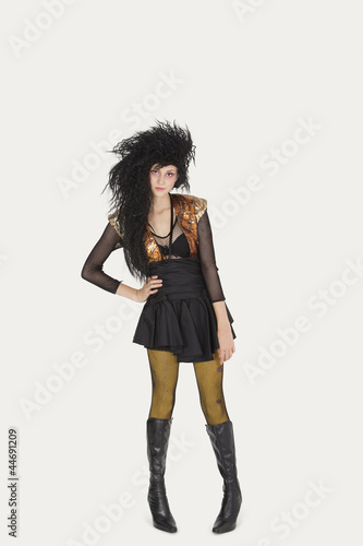 Portrait of young woman in gothic clothing over gray background