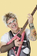 Portrait of happy senior male punk rock musician playing guitar over yellow background