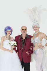 Portrait of man standing arms in arms with senior showgirl and daughter in wedding dress over gray background