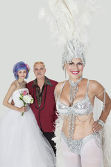 Portrait of senior showgirl with father and daughter in wedding dress against gray background
