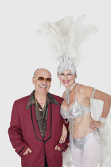 Portrait of man with senior showgirl against gray background