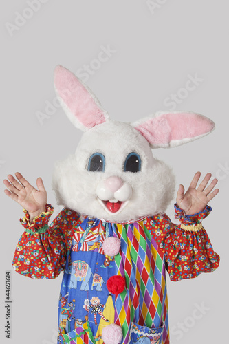 Man wearing bunny mask with standing raised hands against gray background