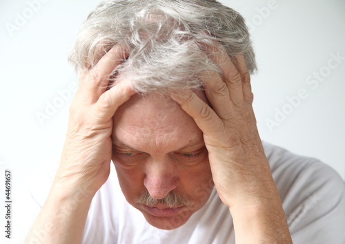senior man holds his head in despair