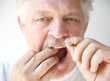 senior man flosses teeth