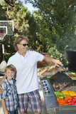 Portrait of a little boy with father barbecuing vegetable on barbecue grill in lawn