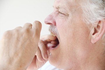 older man flossing teeth profile view
